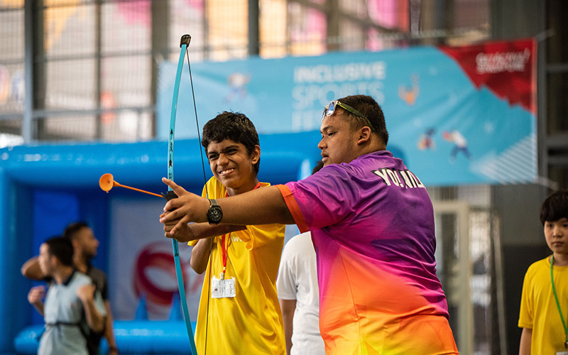 A Team Nila volunteer assisting a participant at Inclusive Sports Festival 2019