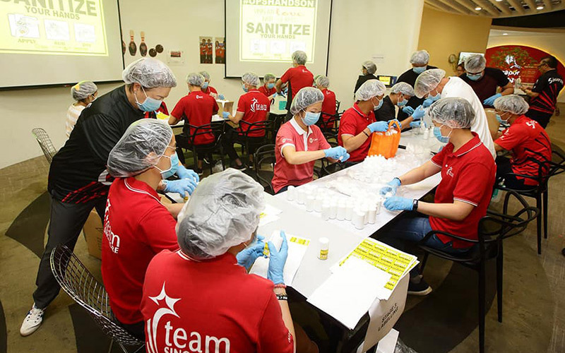 Team Singapore athletes packing sanitiser for care packs
