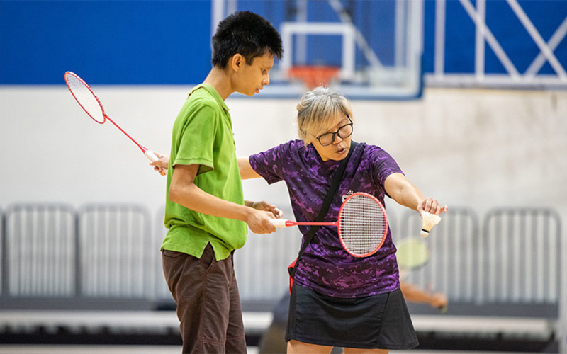A Team Nila volunteer teaching badminton to a Play-Ability participant