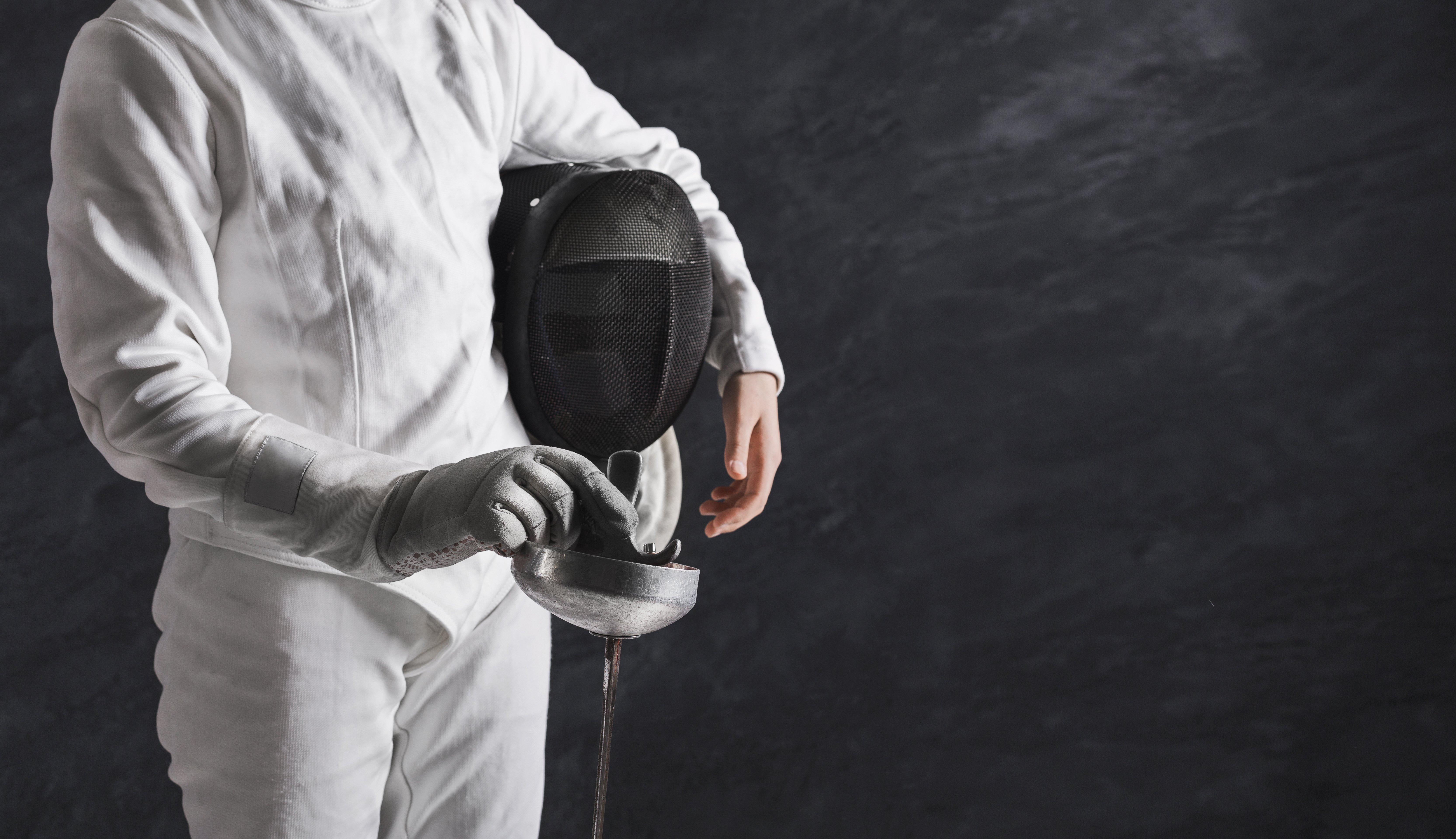 female-fencer-in-white-fencing-suit-at-black-backg-2021-04-02-20-24-50-utc