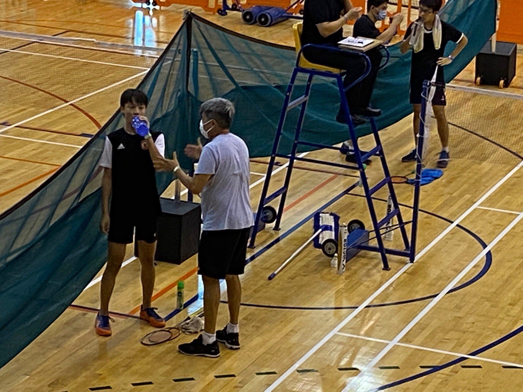 NSG A Div boys badminton - RI vs VJC second singles mid-set break Victor Soh being coached